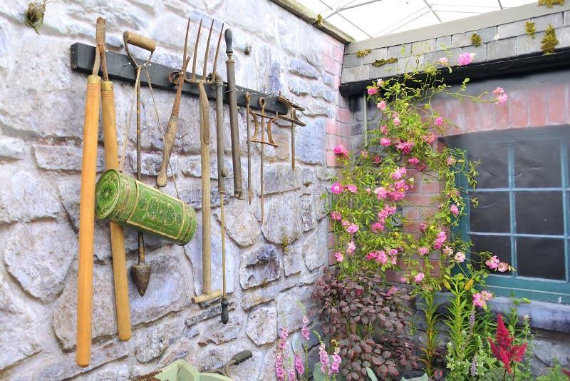 Outils de jardin sur le mur en pierre photos stock