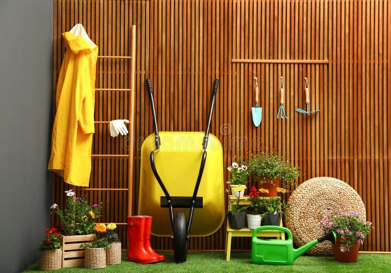 Outils de jardinage avec la brouette et les fleurs photos stock
