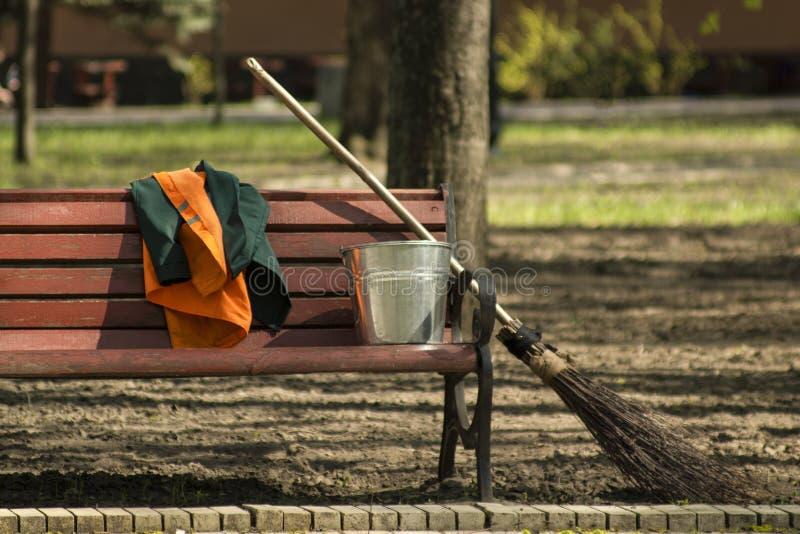 Outils de jardinage de balai et de seau et uniforme de travailleurs sur un brench photo stock