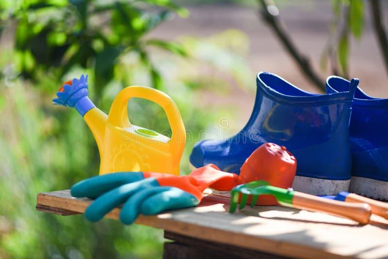 Outils de jardinage sur le conseil en bois avec l'équipement de truelle de gants de jardin de botte en caoutchouc et la boîte d'a photos libres de droits