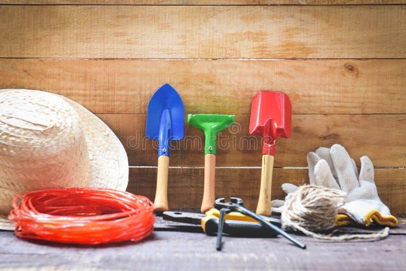 Outils de jardinage sur le fond en bois avec des pinces chapeau de paille, corde, équipement de jardin de truelle de gants photo libre de droits