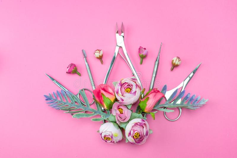 Outils de manucure sur un fond rose d?cor? des fleurs photographie stock