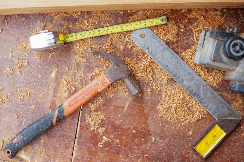 Outils de menuiserie de vue supérieure sur le bureau en bois sale avec la sciure image libre de droits