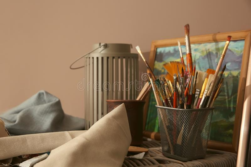 Outils de peinture avec l'image sur le panier en osier dans l'atelier de l'artiste images libres de droits