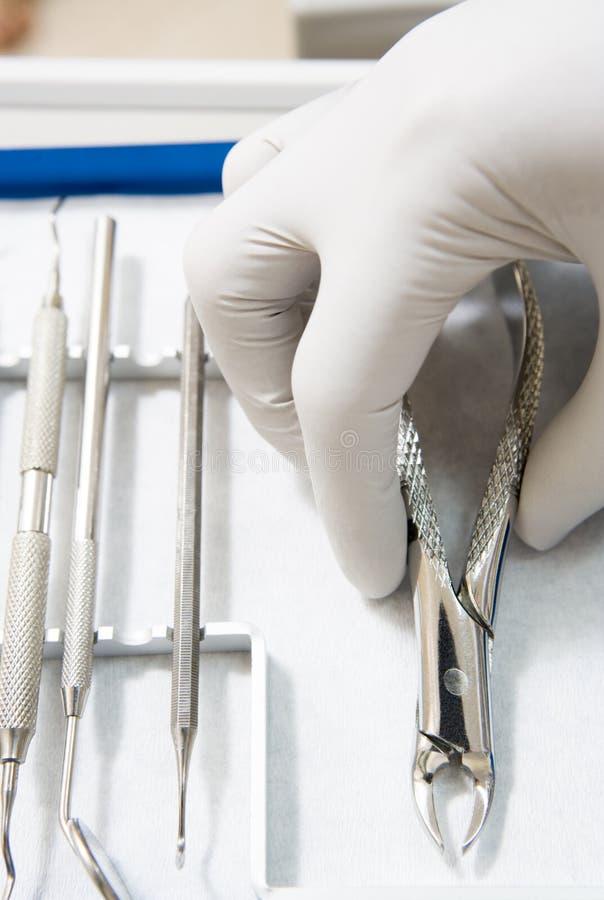 Outils dentaires avec une main enfilée de gants photographie stock libre de droits