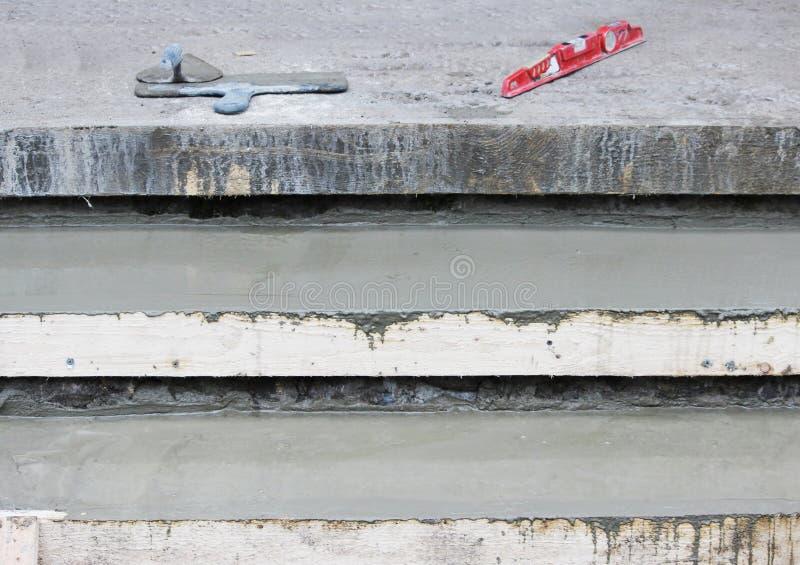 Outils : Deux truelle, niveau sur les étapes et coffrage en bois ont rempli de mélange de béton images libres de droits