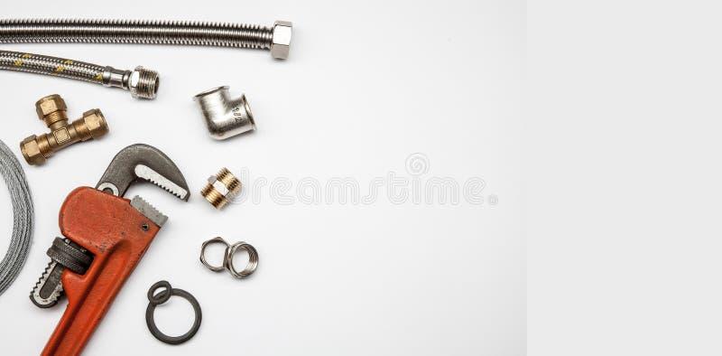 Outils et équipement de tuyauterie sur le fond blanc avec l'espace de copie photos stock