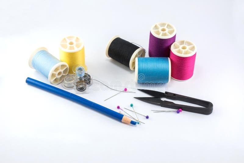 Outils et accessoires de couture avec les fils colorés sur le fond blanc images stock