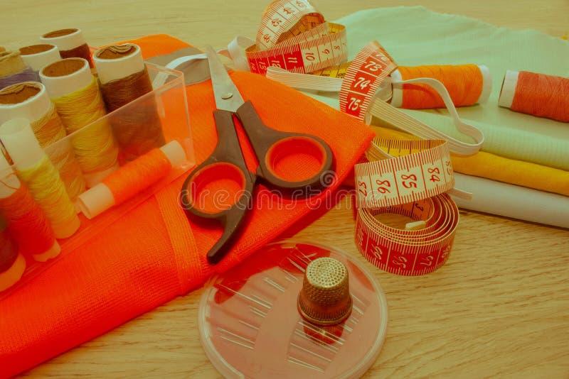 Outils et kit de couture de couture sur le fond texturisé en bois Sewin images libres de droits