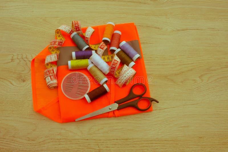 Outils et kit de couture de couture sur le fond texturisé en bois Threa photographie stock