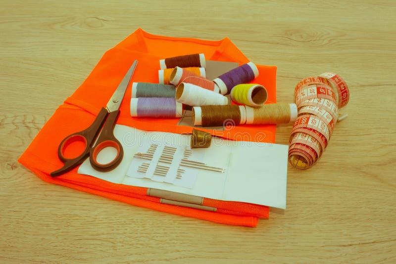 Outils et kit de couture de couture sur le fond texturisé en bois Threa images libres de droits