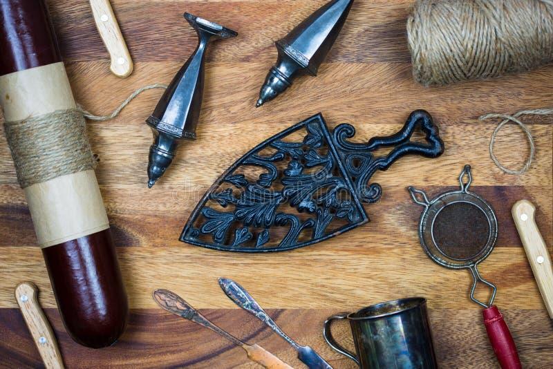 Outils et saucisse antiques de cuisine avec le conseil en bois photo stock