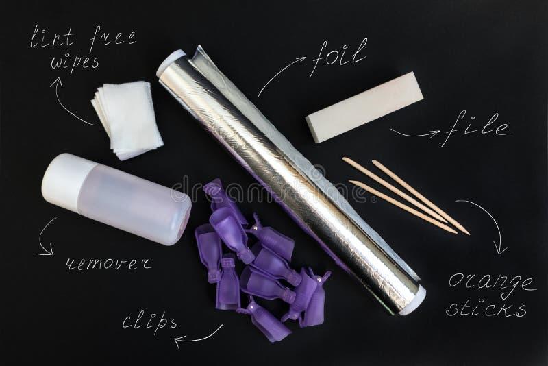 Outils pour enlever le poli UV de gel à la maison sur un fond noir photographie stock libre de droits