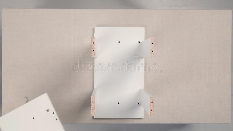 Outils pour l'ensemble de meubles barre Les meubles se réunissants, mains dans les gants se ferment pour serrer la vis de meubles photographie stock libre de droits