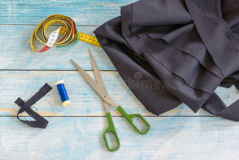 Outils pour la couture : le tissu, ciseaux, goupilles, ruban métrique sur la vue supérieure de fond en bois bleu, configuration p photo libre de droits