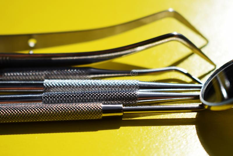 Outils pour le traitement dentaire sur un fond jaune photo libre de droits