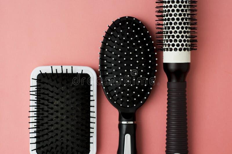 Outils utilisés de brosse de cheveux sur le fond rose ou de corail avec l'espace de copie Mode de beauté, fond de soins capillair image libre de droits