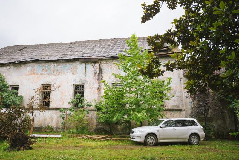 Outlander blanco de Mitsubishi Airtrek del coche parqueado cerca del edificio lamentable abandonado, imagenes de archivo