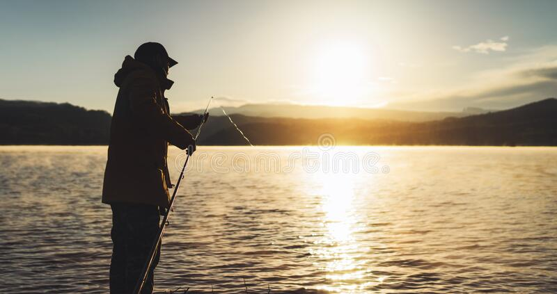 Outline fisherman fishing rod at sunrise sunlight, man enjoy hobby on evening lake, person catch fish on background night. Sky, relaxation vacation fishery stock image