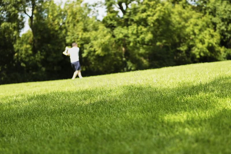 Outline man playing ball and bat in park on green grass stock images