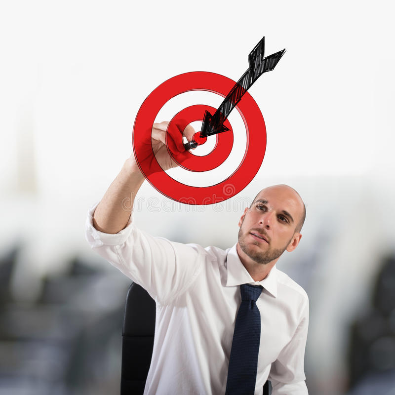 Outline your goals. Businessman drawing a target with the arrow. Outline your goals concept royalty free stock image