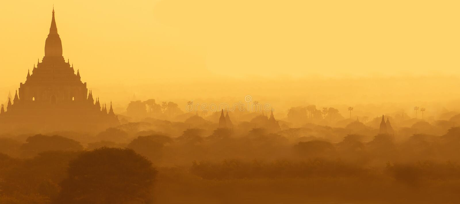 Outlines of an ancient Buddhist temples in Bagan, Myanmar in the morning mist. Aerial view. Panoramic landscape. Copy space royalty free stock images
