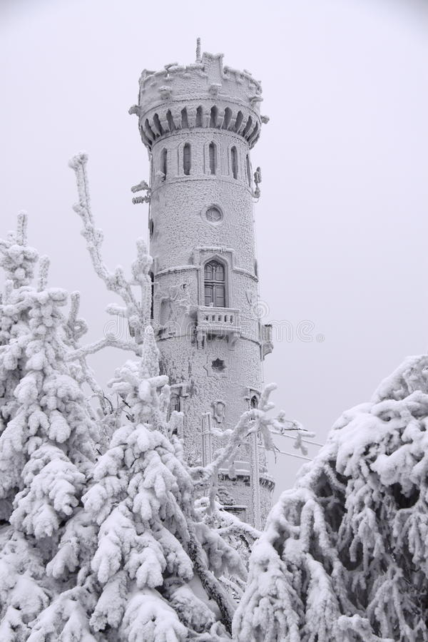 Outlook tower in the middle of winter. Ancient snow covered tower between trees stock image