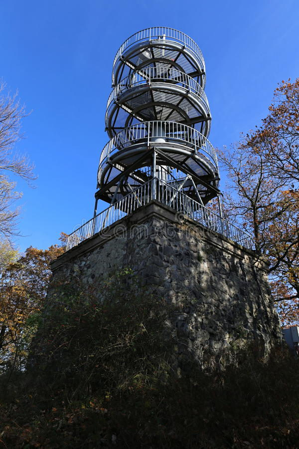 Outlook tower with three plates. Modern metal outlook tower with three rounded levels on the stone block stock photo