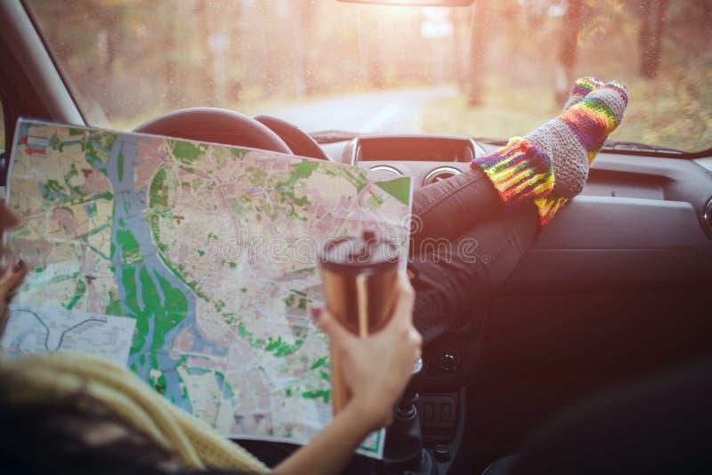 outono, auto curso Cose-up de beber da mulher leva embora o café do copo durante a viagem por estrada em um carro As verificações foto de stock