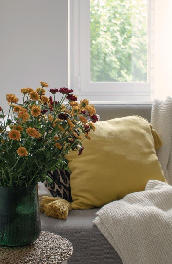 outono escandinavo decoração inspirada da casa - close up do ramalhete das flores dos mums, sala de visitas acolhedor, Sofa Cushi imagens de stock