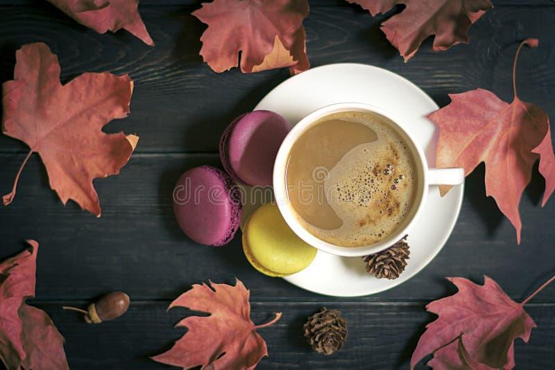 outono, folhas da queda, copo cozinhando quente de cafés do cappuccino, bolinhos de amêndoa, cones no fundo de madeira da tabela fotografia de stock
