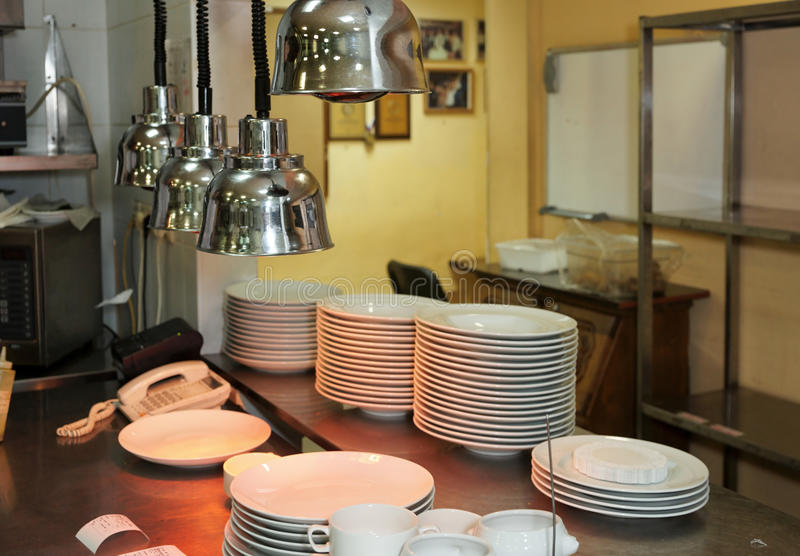 Output zone of a commercial kitchen. With infrared lamps to keep plates warm royalty free stock photo
