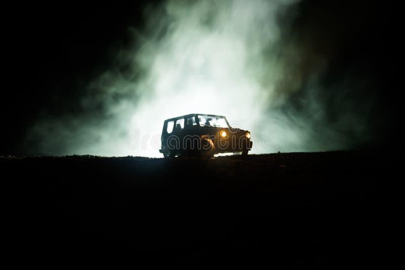 Outre de la silhouette de jeep de roader sur le fond brumeux modifié la tonalité foncé de ciel Voiture avec la lumière la nuit image stock