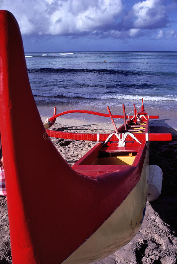 Outrigger boat on Oahu Beach in Hawaii. Image shows an outrigger boat on Oahu Beach in Hawaii. Boat is used by local Hawaiians to provide tourists a wave riding royalty free stock images