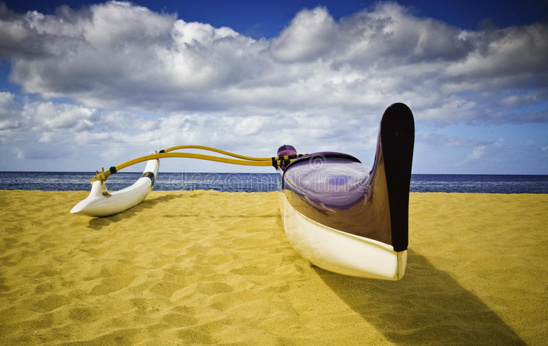 Outrigger Canoe. A solitaire fiberglass outrigger canoe on sandy beach looks out towards the horizon and cloudy skies stock images