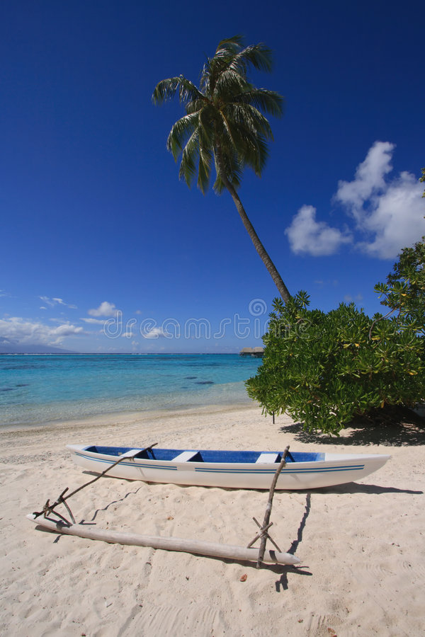 Outrigger Canoe on Beach. Outrigger canoe on beautiful beach with turquoise water royalty free stock photography