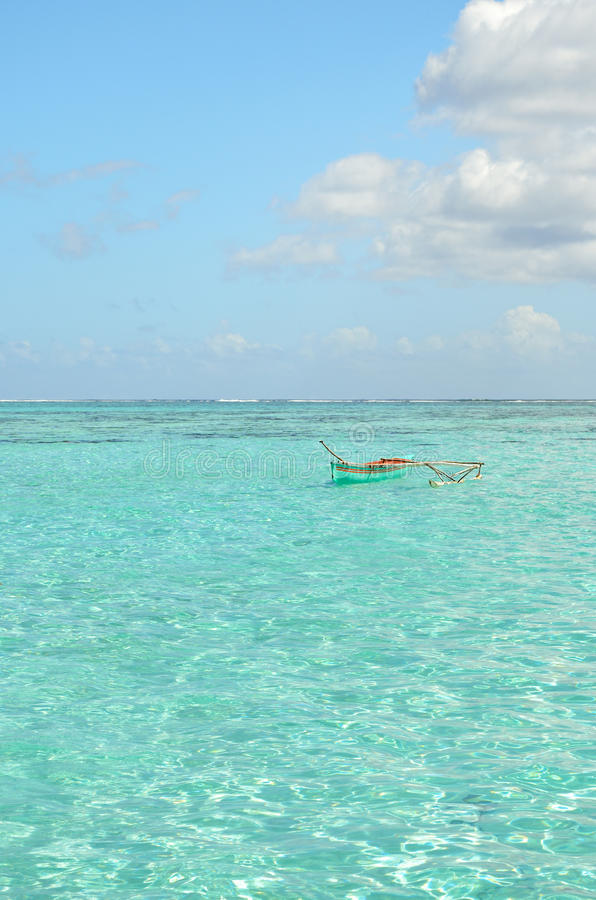 Outrigger canoe in clear lagoon water stock photo