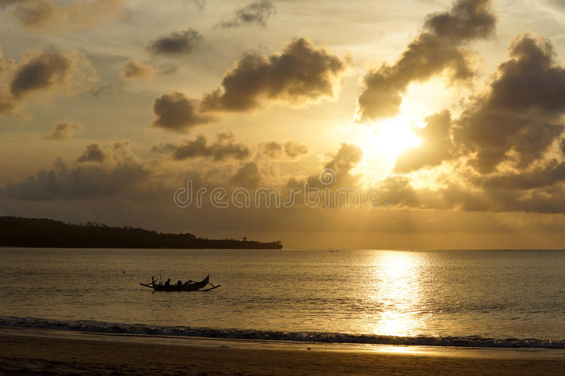 Outrigger canoe on a sunset ocean stock images