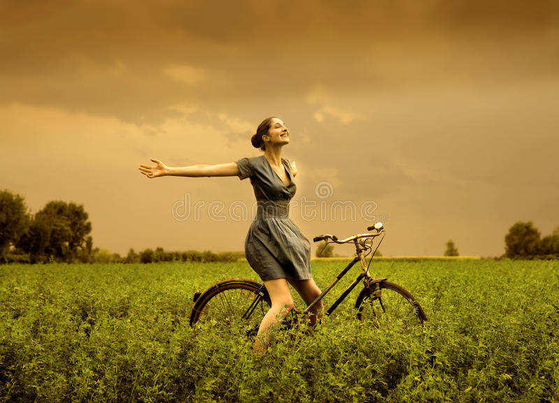 Outside. Beautiful girl riding bicycle in the countryside