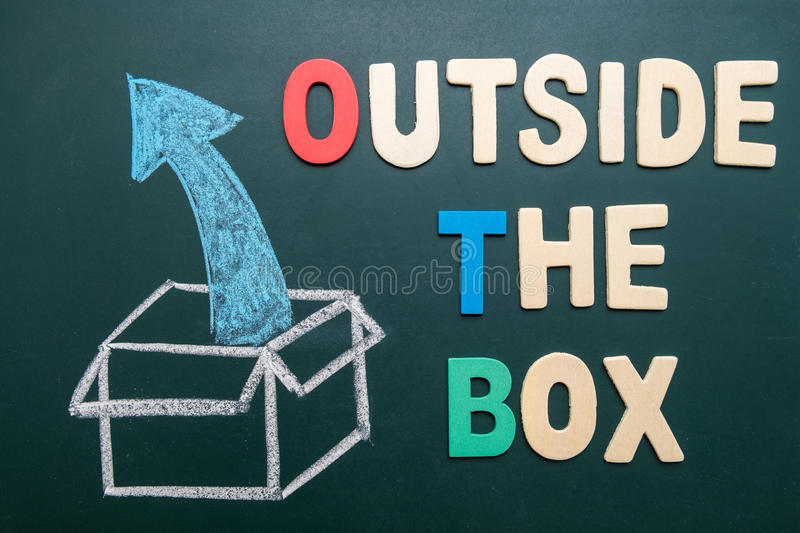 Outside the box - business concept of comfort zone. Outside the box wording with image drawing of box and arrow on blackboard - business concept of getting out stock photography
