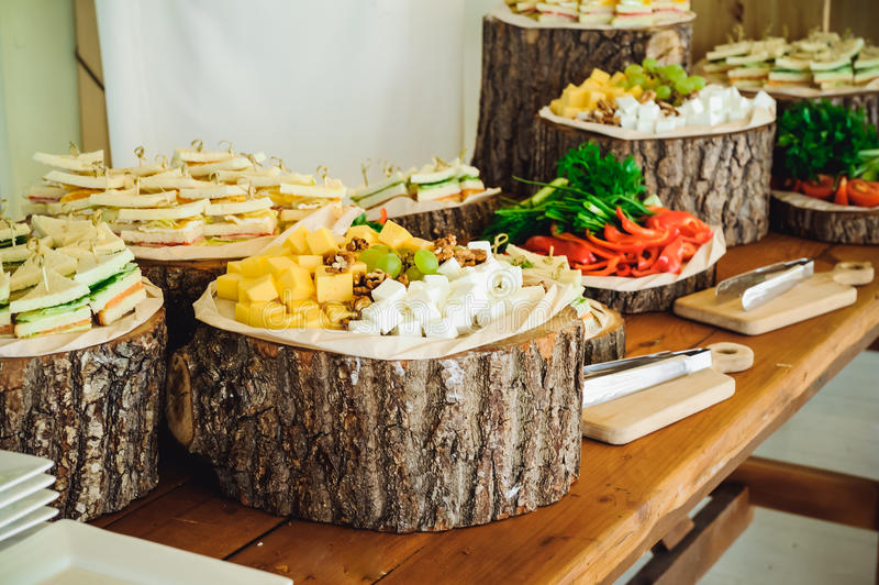Outside Catering buffet table with a delicious food for guests of the event in rustic style. Service at business meeting, party, w. Eddings. Selective focus royalty free stock images