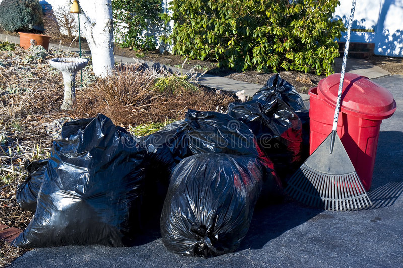 Outside Cleanup. Bags of leaves,trash container,and rake sitting in driveway after yard cleanup stock photography