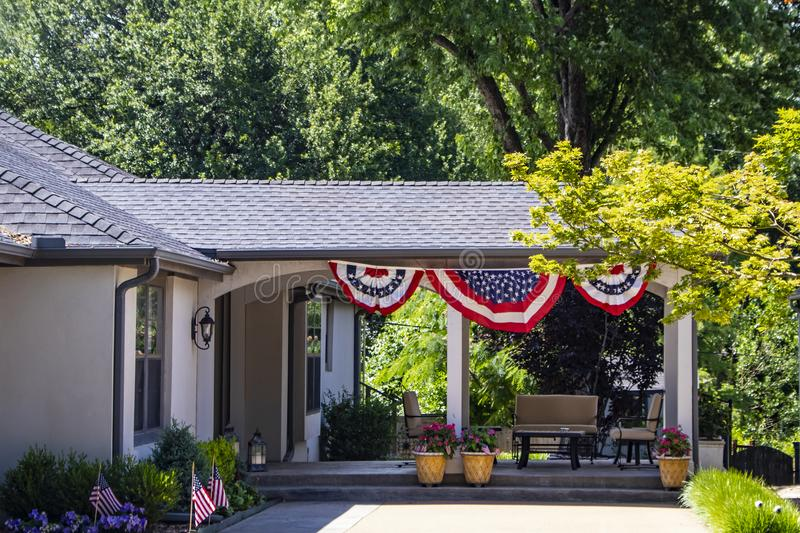 Outside covered patio with furniture and patriotic Forth of July bunting and American flags stuck in flower bed and pots. An Outside covered patio with furniture stock photo