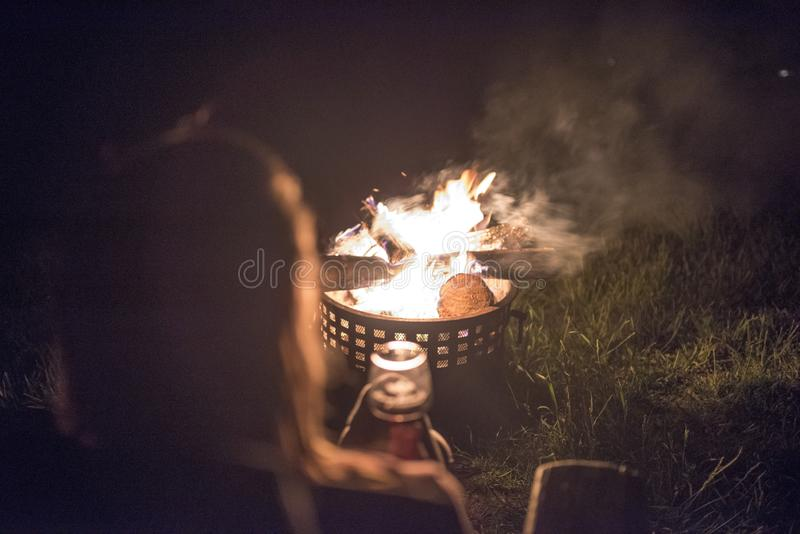 A woman with long hair enjoys wine and a warm outside fire stock image