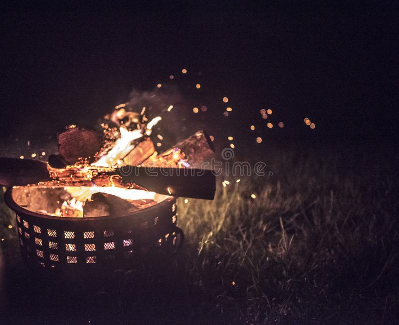 Outside fire inside of a fireproof canister on grass stock photo