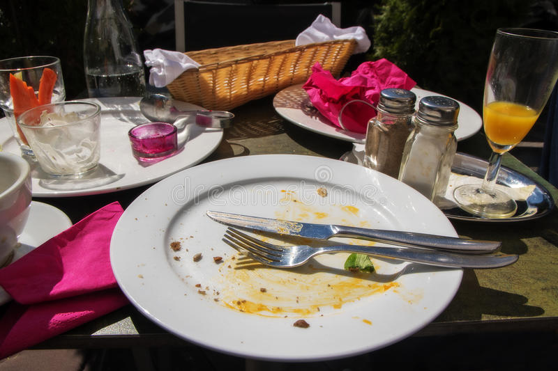After the outside meal, table set with an empty eaten food plate. Cutlery, pink napkins, empty bread basket and various dishes, selected focus, narrow depth of royalty free stock photo