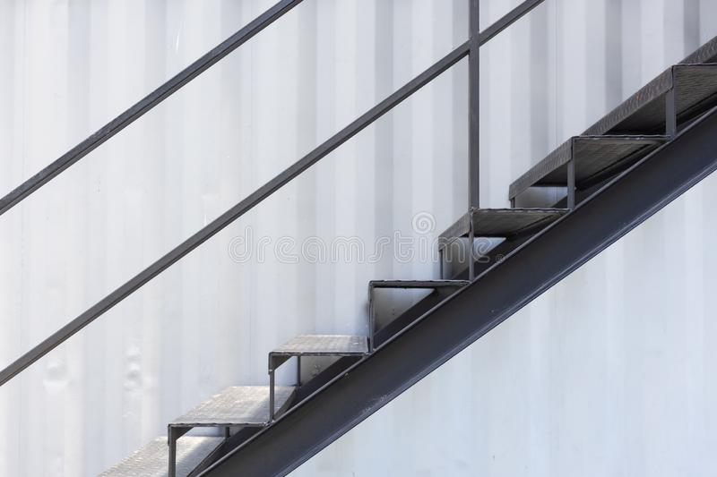 Outside metal staircase or fire exit stair with sheet corrugated wall background royalty free stock photography