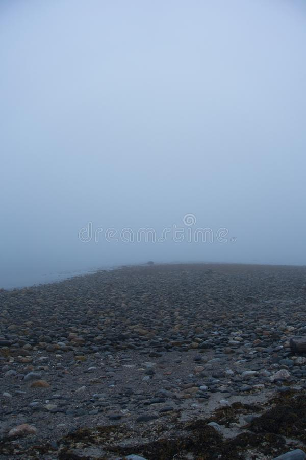 Outside nature photo featuring fog and rocks along a coast line stock images