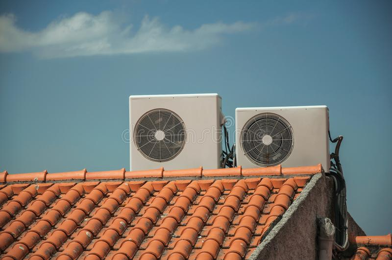 Outside part of air conditioning installation on rooftop. Outside part of air conditioning installation on house rooftop, in a sunny day at Linhares da Beira. A royalty free stock photography