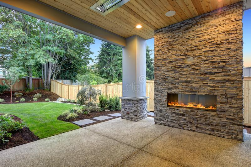 Outside Patio boasts gorgeous stone Fireplace. Outside Patio features natural wood plank ceiling, concrete floor and oversized stone fireplace overlooking a stock photography